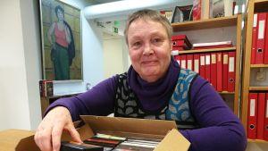 """Elina Sana skrev boken """"Kuolemanlaiva s/s Hohenhörn"""". Det gjorde hon 1979. Här på Kansan Arkisto med de c-kasetter hon bandade in."""