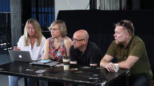 Käsikirjoittaja Johanna Hartikainen ja käsikirjoittaja-ohjaajat Ulla Heikkilä, Matti Kinnunen ja Juha Kukkonen istuvat pöydän äärellä rivissä kahvimukit ja läppäri edessään.