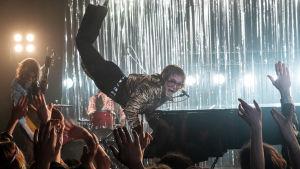 Elton John (Taron Egerton) spelar piano och börjar sväva upp i luften.