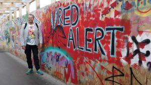 """En man står invid gatukonst på en tillfälllig träbro. Det står """"Red Alert"""" på väggen. Mannen har fritidskläder och ryggsäck. Han ler lite."""