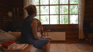 Johanna Crafoord sitter på en soffa med ryggen vänd mot kameran, och ser på det fönster som krossades av vandaler.