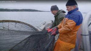 Två män drar i en ryssja på en båt.