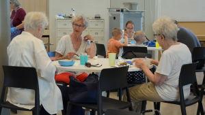 Tre äldre damer i vita skjortor sitter runt ett bord och äter och pratar