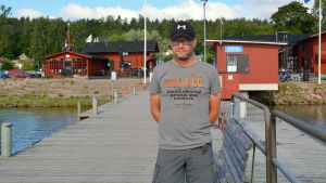 En man står på en brygga framför röda bodar.