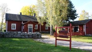 Ett rött trähus bakom en stenmur. Framför huset finns en röd skylt där det står Sockenstugan.
