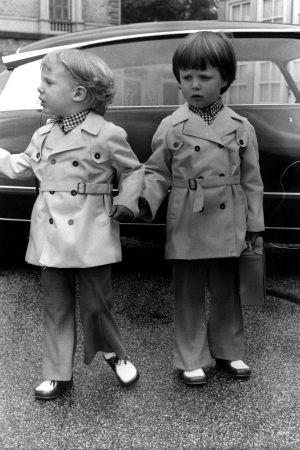 Två småpojkar i trenchcoat poserar framför en bil