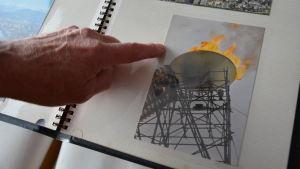 Ett finger visar i ett fotoalbum på en bild av den olympiska elden vid de olympiska vinterspelen i Grenoble 1968.