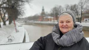 Lena Sarlin, en dam med grånande hur, grå mössa och en svartvitrutig halsduk står vid ett snöigt broräcke. I bakgrunden syns Aura å och Åbo Domkyrka.