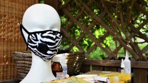 Vitt dockhuvud med zebramönstrat munskydd framför mundelen.