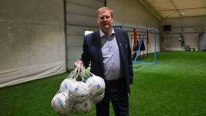 Folke Lindström håller i en nätkass med fotbollar.