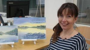 Konstnären Victoria Yaroshik framför två havsakvareller