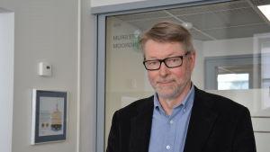 Per-Olof Karlsson i halvbild med skägg, glasögon och mörk kavaj.