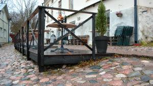 Café Fannys träterrass byggt på sluttande mark med runda stenar