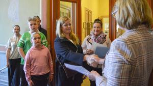 sammanbitna föräldrar överräcker en namnlista till bildningsnämndens ordförande