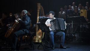 Lelo Nika på dragspel tillsammans med kör och orkester.