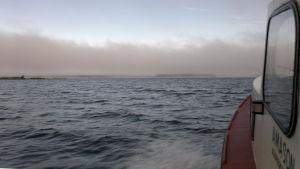 Båt rör sig i skummande vatten mot en dimhöljd horisont.