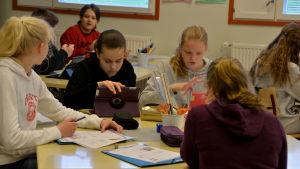 Fyra flickor sitter runt ett bord och jobbar. Skriver och läser på sin tablett.