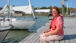 Seija Lindeberg sitter på bryggan vid gästhamnen i Pargas.