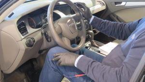 En man sitter inne i en bil, man ser inte ansiktet. Däremot ser man att han har svarta gummihandskar på sig som skydd. Händerna är delvis på ratten.