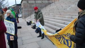 Klimatdemonstranter på riksdagens trappa sätter upp en banderoll.