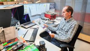 En man sitter vid ett skrivbord i ett kontor och tittar på ett papper.