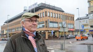 Man i keps framför affärshus i centrala Borgå en grå novemberdag
