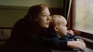 Astrid och sonen Lasse tittar ut genom tågfönstret på väg genom Sverige.