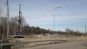 Grundläggningsarbeten, man förbereder en tomt för höghusbyggen vid Brännmalmsvägen i Sjundeå. En stor lyftkran eller lift och på håll kan man skönja lastbilar. Annars tom tomt utan träd invid en asfalterad väg.