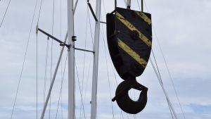 En krok till en lyftkran hänger framför några segelbåtsmaster.