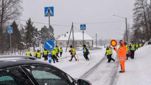 Elever går tryggt över landsvägen då trafiken får vänta.
