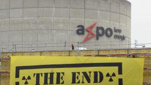 Schweiziskt kärkraftverk med Greenpeace banderoll i förgrunden.
