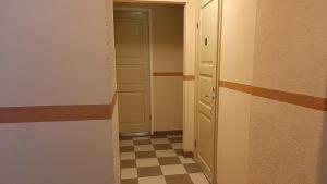 Källarkorridor i förnyade Heideken. Rutigt golv i brunt och vitt. dörrar och golv i ockrabrunt och olika rödgula nyanser.