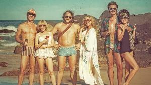 Seurue poseeraa beachillä 1970-luvun vetimissä. Kuva elokuvasta Liekehtivät lapset.