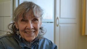 Äldre kvinna med grått hår ler mor kameran.