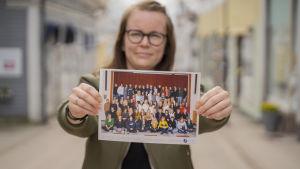 En kvinna håller fram och visar ett klassfoto.