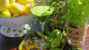 Grön dryck i cocktailglas dekorerad med två basilika blad.