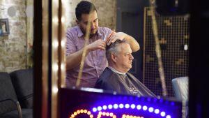 David Eburn sitter fotograferad genom fönstret till en frisörsalong där han får håret klippt.