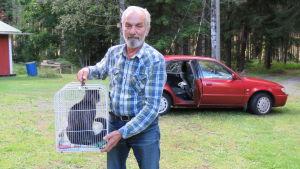 En äldre man med grått hår och skägg håller upp en bur där det finns en katt. Bakom en röd bil. Sommar och gröna träd och gräsmatta.