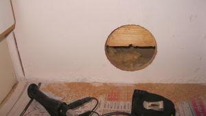 Kosteusongelmia tutkitaan seinään tehdyn reiän kautta.