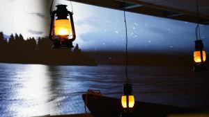 Fotogenlampor lyser. I bakgrunden syns en film där en måne lyser och framför filmduken står en eka.