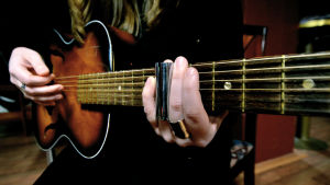 Närbild på en gammal akustisk gitarr som spelas med ett sliderör.
