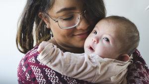 Emilia Jansson håller i dottern Junia som nyfiket tittar upp mot ljuset.