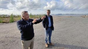 Jan-Erik Chydenius står och visar något med händerna. Jukka Takala står bredvid och tittar. I bakgrunden skymtar det öppna havet.