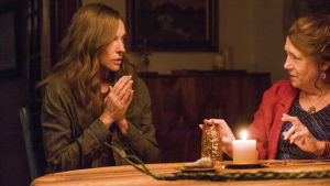 Annie (Toni Colette) och Joan (Ann Dowd) sitter vid ett bord med ett tänt ljus och håller seans.