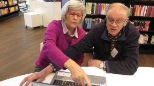 Enter-järjestön vertaisopastaja Raimo Anttila kirjastossa tietokoneen takana, opastettavana Irma Pantzar.