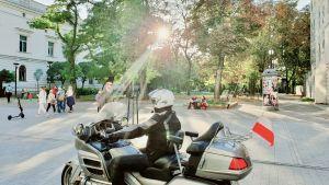 En motorcyklist med en polsk flagga fäst vid cykeln åker längs med staden Lodz huvudgata vid solnedgången.
