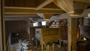 Innanför en gammal kvarn. Allt är i trä, väggar, tak, golv.