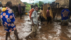 Invånare i en by går längs en översvämmad väg i Moçambique.