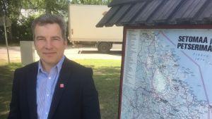 Setomaas kommundirektör Raul Kudre står bredvid en karta över Setomaa i Estland och Petserimaa som i dag ligger i Ryssland.