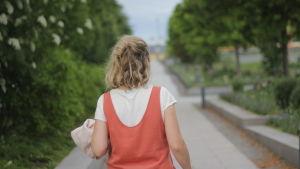 Vit kvinna med ljust hår går med ryggen mot kameran på en gångväg med gröna träd runt.